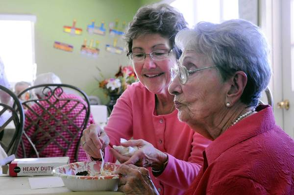 Rose Miranda, celebrating her 87th birthday, gets some help with her cake and ice cream from her daughter, Teresa Miranda.
