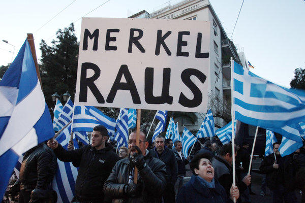 "Supporters of the far-right party Golden Dawn hold up Greek flags and a sign that reads in German ""Merkel get out"" during a protest outside the Germany embassy in Athens."
