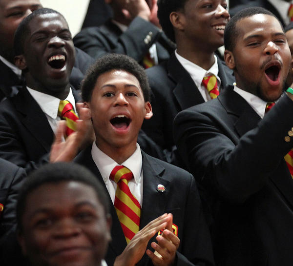 Pravione Winding (center) celebrates with fellow Urban Prep students to mark 100 percent of their graduates being accepted into 4 year colleges.