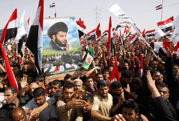 Followers of Iraqi Shiite Muslim cleric Muqtada Sadr carry an image of him and chant slogans against the U.S. and sectarianism during a protest in Kut, 100 miles southeast of Baghdad on March 16, 2013.