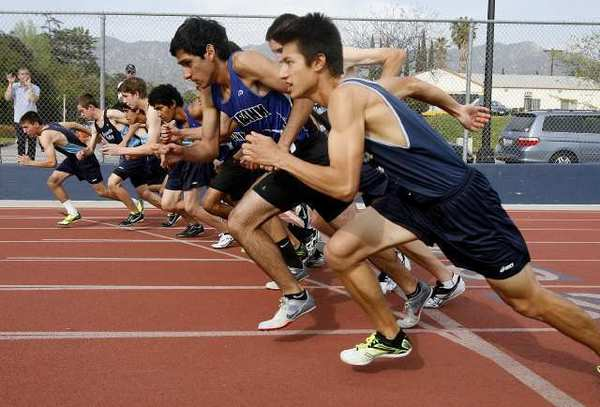 Crescenta Valley and Burbank high runners lean forward at the start of the 800-meter race in a dual Pacific League track meet at Burbank High.