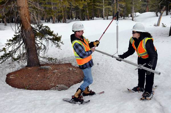 Helicopter pilot Brett Hendricks, left, and hydrographer Christina Bohrman survey the snowpack in the Sierra Nevada. With statewide snowpack at only 52% of the norm for this time of year — when it is usually at its peak — state and federal water managers are expecting below-normal runoff this spring and falling reservoir levels.