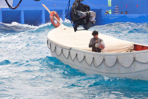 "Actor Suraj Sharma alone on a lifeboat in a water tank against a blue screen in scene from ""Life of Pi,"" for which Rhythm & Hues received an Academy Award."