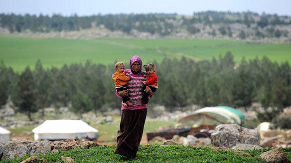 A Syrian woman carries her children near their makeshift refugee camp at the city of Afrin on the Syria-Turkey border.
