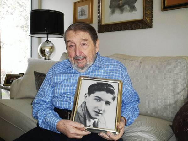 "Abby Weiner of West Hartford, sitting in his living room and holding a portrait of himself as a boy, around the age he was sent to Auschwitz. He was eventually transferred to Buchenwald and lived in the children's block. A movie about that block, ""Kinderblock 66,"" will be shown at the Mandell JCC Hartford Jewish Film Festival."