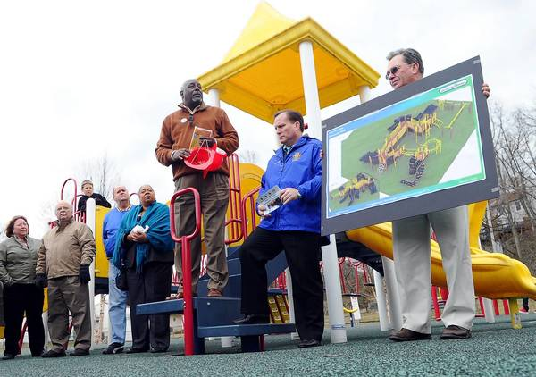 Mike Lhotsky, right, director of Laurel Parks and Recreation, holds an image of the new proposed playground complex for fire-damaged Discovery Community Park, as City Council president Fred Smalls, center, talks about the project during Community Fun Day March 28. At left are Laurel City Council members Donna Crary, Mike Leszcz, Ed Ricks and Valerie Nicholas.