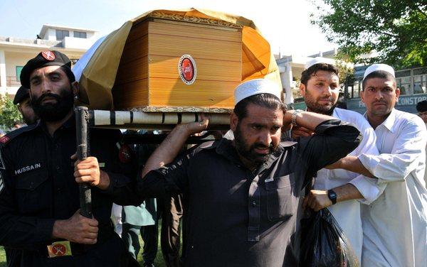 Pakistani Frontier Constabulary officials attend the funeral of their comrade who was killed Friday in a suicide bomb blast in Peshawar targeting the constabulary chief's convoy.