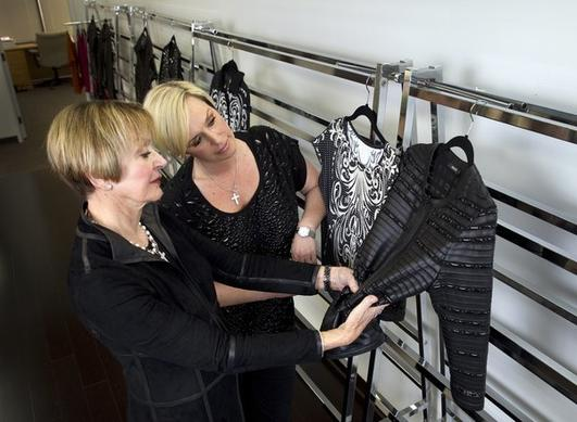 Marie Gray, left, and her daughter Kelly Gray, of St. John Knits women's clothing fame, look at a blouse as they launch