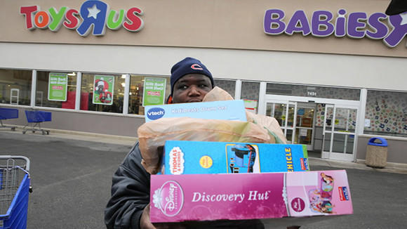 Marlon Alston of Chicago is loaded with presents for his nine-year-old son and five-year-old daughter, Christmas Eve in North Riverside.