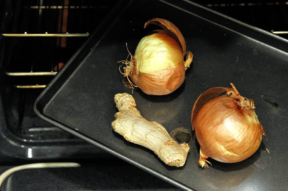 To prepare Charles Phan's beef broth for pho, begin by roasting the onion and ginger in the oven, until the onion is soft.