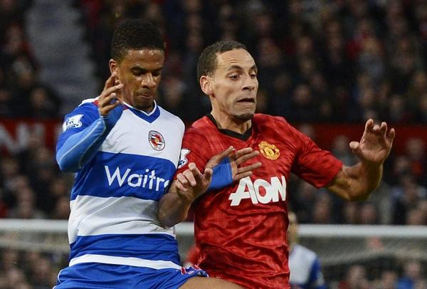 Manchester United's Rio Ferdinand (right) challenges Reading's Garath McCleary during their English Premier League soccer match.