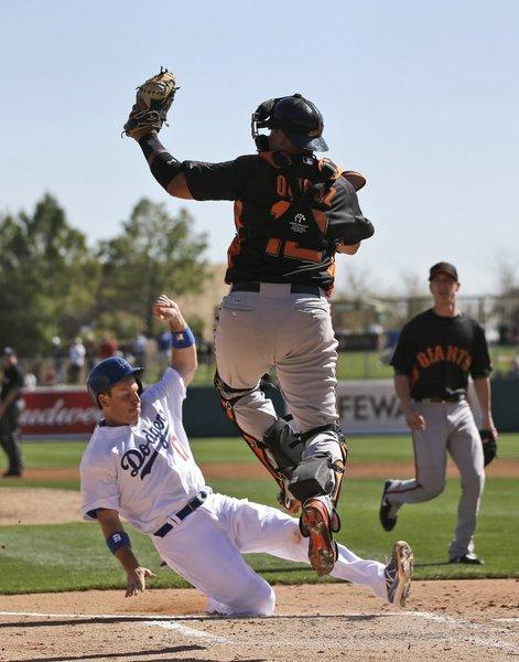Mark Ellis scores on a double by Jeremy Moore as San Francisco Giants catcher Guillermo Quiroz catches a high throw during the second inning of an exhibition spring training baseball game on Tuesday, Feb. 26, 2013 in Glendale.