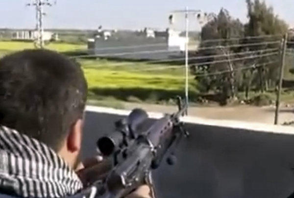 This image taken from video obtained from Ugarit News, which has been authenticated based on its contents and other Associated Press reporting, shows a fighter with the Syrian Free Army firing on a Syrian army position in Dael, near the Jordanian border.