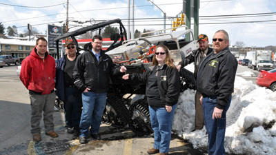 The Bakersville Volunteer Fire Department added a new utility terrain vehicle to its fleet Friday. From left are Adam Walker, foreman; Willie Walker, second assistant chief; Jeremy Salyers, Highland Harley-Davidson salesman; Trish Stahl, secretary; state Rep. Carl Walker Metzgar; and Dave Stahl, chief.
