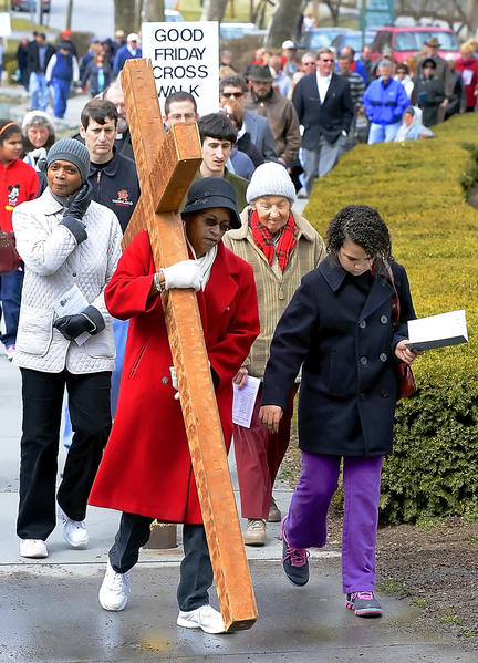 Susie Wright carries the cross beside her grandaughter, Rayana Ford, around the lake at City Park during the Hagerstown Good Friday Cross Walk.