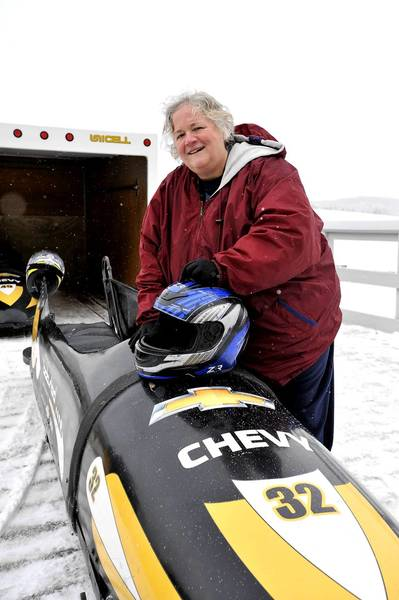 Reporter Diane Stoneback stands next to a bobsled that will take her down a half-mile run at the Lake Placid Bobsled Experience.