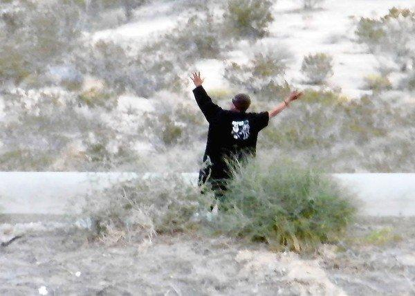Steven Brooks raises his arms as he is arrested near Barstow after a police chase. Hours earlier, he had been expelled from the Nevada State Assembly.