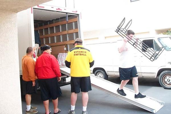Coach Mike Bargas, Chuck Perry, Mayor Pro Tem Tom Mensinger and player Mac Collins, left to right, unload a truck of household good for Tammy Gavel. Bargas and Mensinger took the opportunity to teach the kids about voluntering time in the community.