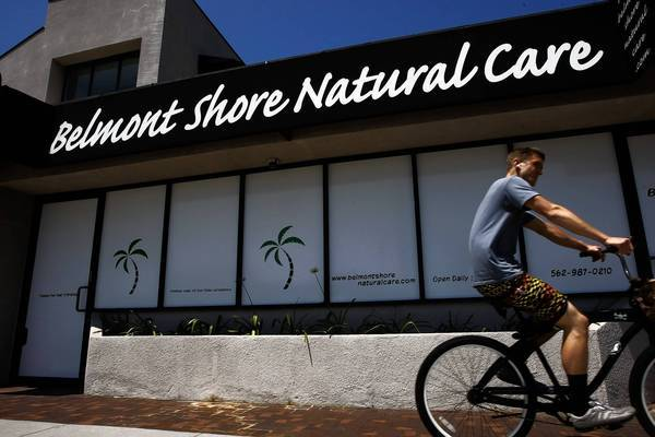 A bicyclist passes Belmont Shore Natural Care, one of nine stores secretly owned by John Melvin Walker.