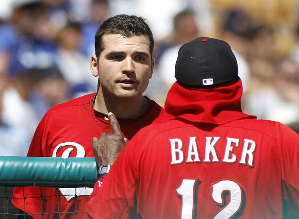 Reds' Joey Votto talks with manager Dusty Baker after scoring against the Dodgers.
