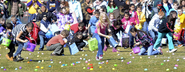 Children rush out onto the outfield of Municipal Stadium for Lifehouse Church's Easter Egg Hunt held Saturday.