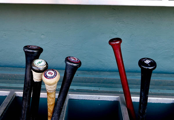 A view of Nationals batting helmets and bats in the dugout before a spring training game.