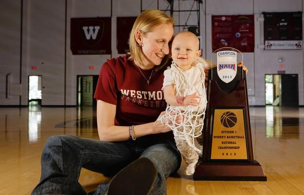 Westmont College women's basketball coach Kirsten Moore and 9-month-old daughter Alexis, wearing the net cut down after the title game.