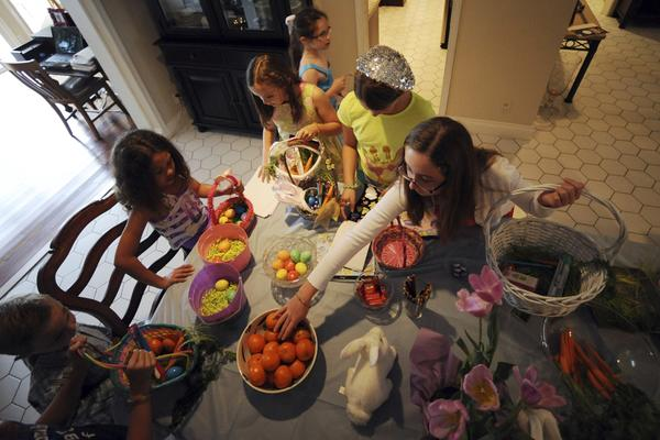Ashley Zorovich reaches for a few clementines to fill her Easter basket. Some parents have tired of the candy deluge at Easter and are making alternative Easter baskets filled with health-conscious items, such as apples, carrots and arts and crafts projects.