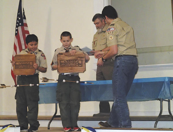 Webelo Scouts from Cub Scout Pack 34 earned their Arrow of Light award recently at the annual Blue and Gold ceremony on March 9. Webelos Joshua Macias and Sean Maguire earned the award, which is the highest award that can be earned in Cub Scouting and is the only Cub Scout award that can be worn on the Boy Scout uniform. Pictured are Scot Arasmith (Cubmaster) and Noel Macias (Webelos leader) presenting the plaques and awards. The two Scouts also crossed over to Boy Scout Troop 412, which is sponsored by Paramount Baptist Church in Hagerstown.
