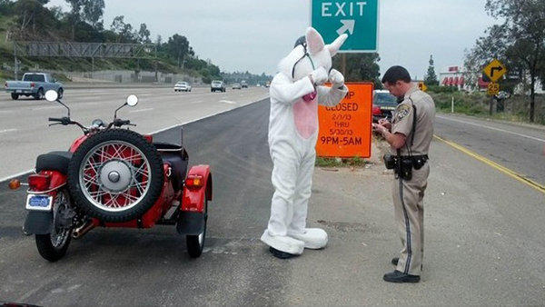 A motorcyclist lacking a helmet is stopped by a California Highway Patrol officer.