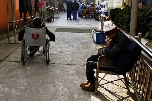 Residents warm themselves in the sun at a retirement home near Shanghai. China has enacted a law requiring children to visit parents and that employers give the children time off to do so.