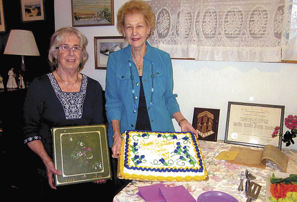 Beverly Kriner, left, Sigma Chapter president, and Patricia Leonard, Sigma charter president, display items marking the 37th anniversary of Sigma Chapter of Alpha Delta Kappa's Founder's Day.