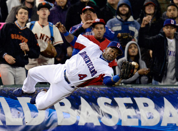 Miguel Tejada of the Dominican Republic dives to make a catch in foul territory against Puerto Rico in the World Baseball Classic.