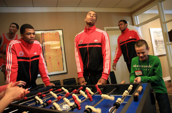 McDonald's All-American Andrew Harrison watches as his brother Aaron Harrison react to losing at foosball with Cooper Cunningham, 10, during a visit to Ronald McDonald House in Chicago.