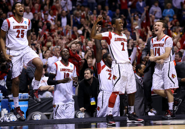 (L-R) Zach Price #25, Gorgui Dieng #10, Russ Smith #2 and Logan Baumann #14 of the Louisville Cardinals celebrate in the final minute of the second half against the Duke Blue Devils during the Midwest Regional Final round of the 2013 NCAA Men's Basketball Tournament at Lucas Oil Stadium on March 31, 2013 in Indianapolis, Indiana.