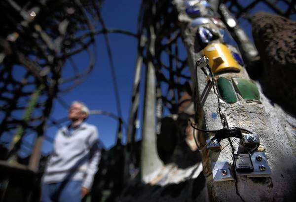 LACMA conservation scientist Frank Preusser examines the Watts Towers structures. At right, electronic devices monitor cracks in the concrete-covered posts.
