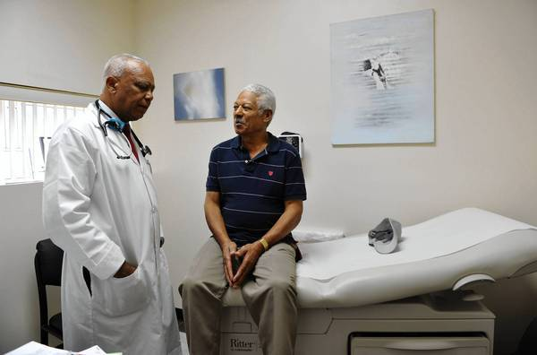 Dr. Sixto Caro treats a patient at a clinic in a Dominican neighborhood of Brooklyn, N.Y. Latinos are among the strongest backers of President Obama's healthcare law.