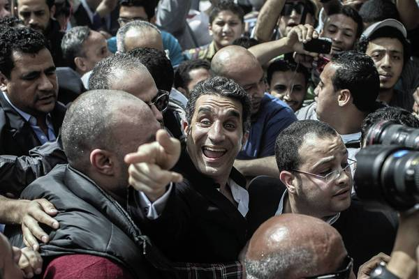 Bassem Youssef, an Egyptian TV satirist often compared to Jon Stewart, is surrounded by media and activists as he arrives to face charges of insulting President Mohamed Morsi.
