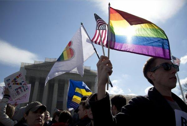 Kevin Coyne of Washington, D.C. holds flags in front of the Supreme Court on March 27.