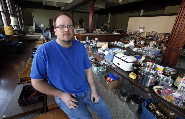 David Land of Aberdeen sits among the many garage sale items he helped put out, one of the many jobs he has done as a day laborer.