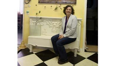 Deer Creek Junk owner Karen Brennan is shown with a bench she created using a footboard.