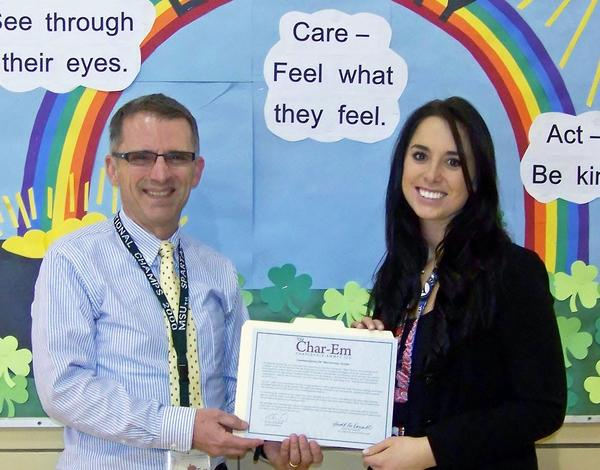 Charlevoix-Emmet Intermediate School District AmeriCorps Program Director Dennis Halverson gives AmeriCorps member Kate Bolton a Certificate of Meritorious Service from the Char-Em school board for her quick actions helping a Lincoln Elementary School student in breathing distress.