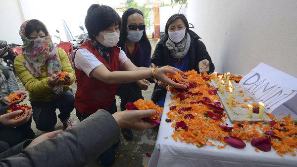 Foreign tourists offer flowers in Bodhgaya, India, last year in remembrance of an Indian woman who died after being gang-raped in a moving bus in December.