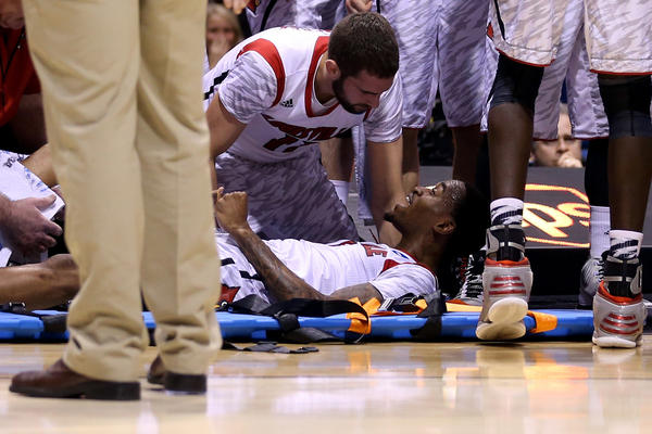 Kevin Ware of the Louisville Cardinals talks with teammate Luke Hancock as Ware is tended to by medical personnel after he injured his leg in the first half against the Duke Blue Devils during the Midwest Regional Final.