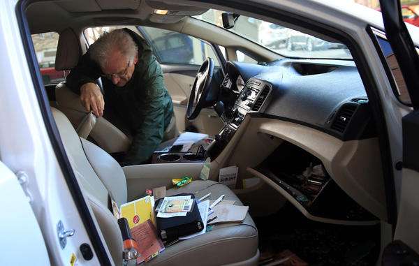 Paul Munson of Richmond, Virginia, looks through his car Monday morning, after is was broken into overnight. Munson's and about 20 other cars were broken into Sunday night in a gated parking lot on the 1300 block of South Wabash Avenue in Chicago. Munson was visiting his two daughters and grandchildren.