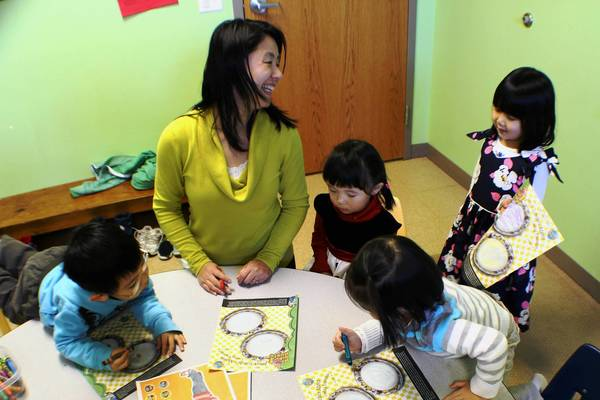 Lin Xin, a first generation Chinese immigrant, teaches Sunday school to children recently at the North Shore Chinese Christian Church, Deerfield.