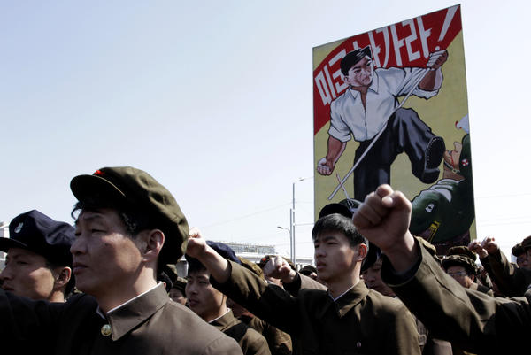 North Koreans punch the air during a rally at Kim Il Sung Square in downtown Pyongyang, North Korea.