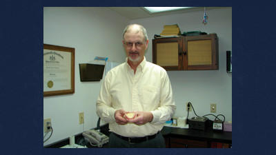 Dr. Joseph Jurgevich holds a sample of a denture anchored by dental implants in his office in Berlin.