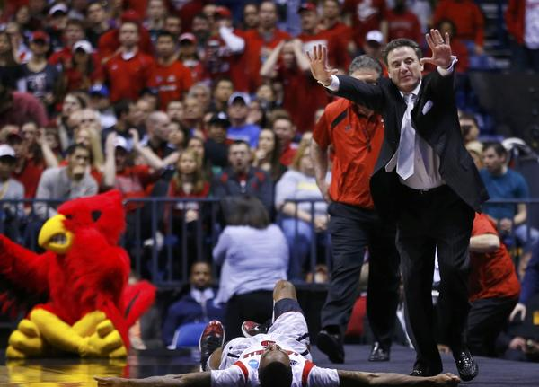 Louisville Cardinals head coach Rick Pitino calls to the referees to stop the game as Cardinals guard Kevin Ware lays on the court with a broken leg.
