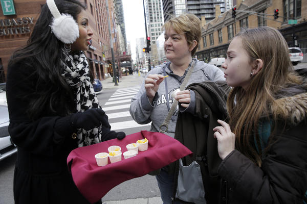 Food blogger Vani Hari offers the UK version of Kraft Macaroni & Cheese, called Kraft Cheesy Pasta, to Kristin Bonner, of Warsaw, Ind., and her daughter Bronwyn Bonner on State and Ohio streets as part of a petition drive to get Kraft to change the U.S. formula of the product and remove dyes not used in the UK meal.